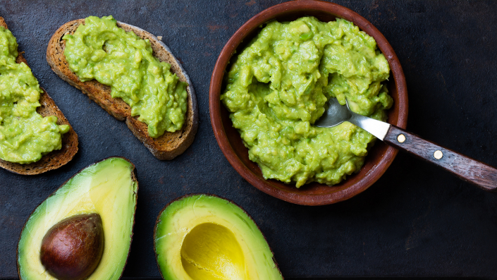 avocado e guacamole con pane su tavolo scuro