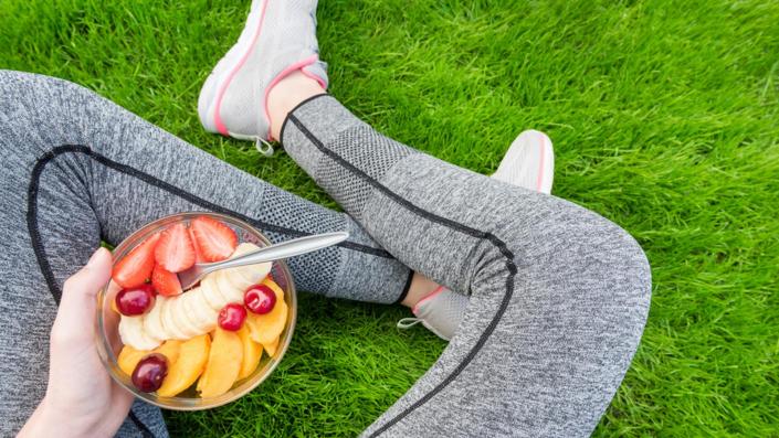 ragazza mangia macedonia frutta sul prato