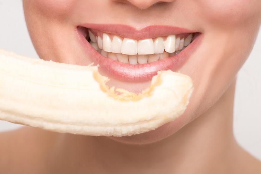 denti bianchi donna con rossetto e banana con morso
