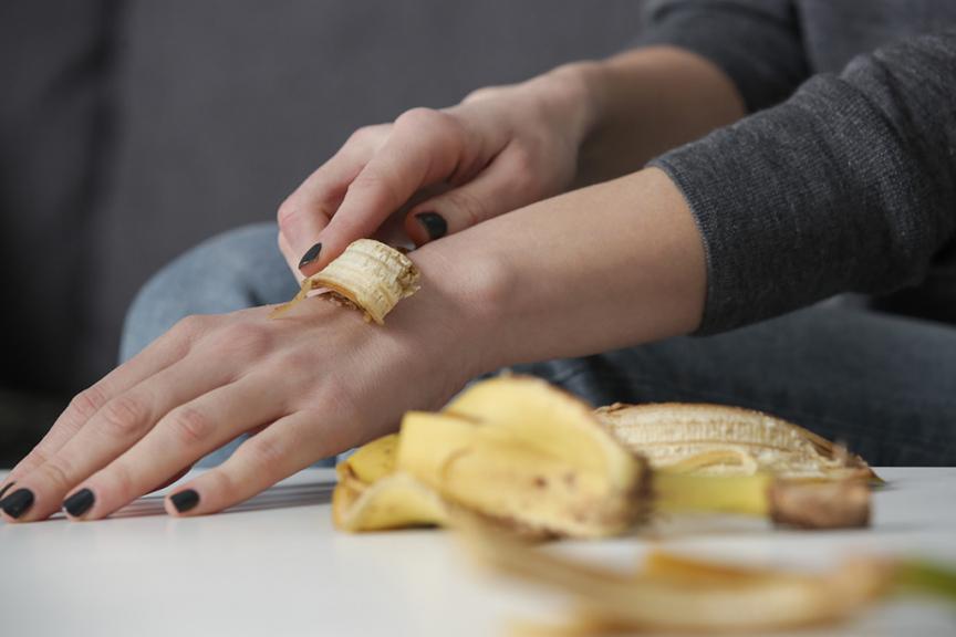 donna poggia su mano con smalto un pezzo di buccia di banana