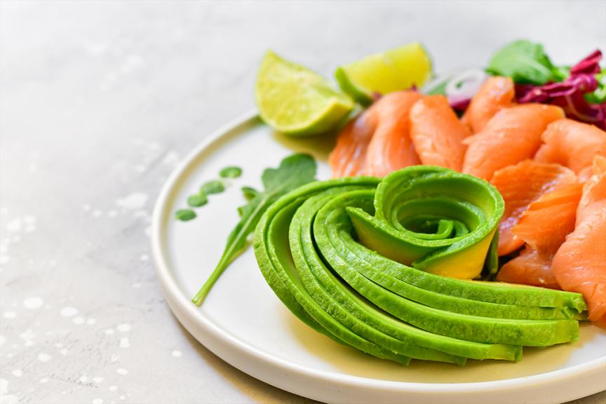 piatto con avocado a fettine e fette di salmone affumicato