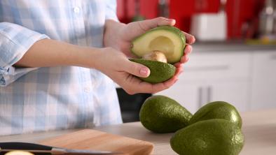 Mani donna reggono avocado tagliato in due