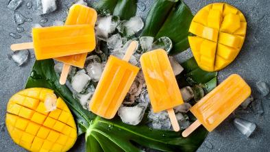 sorbetti al mango con foglia larga e ghiaccio su tavolo scuro