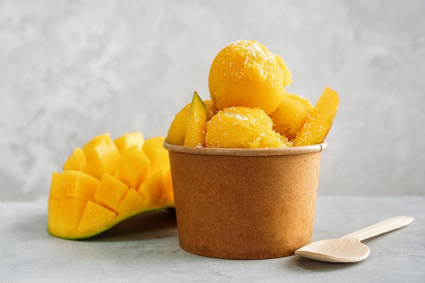 coppetta con sorbetto al mango arancione e mango aperto