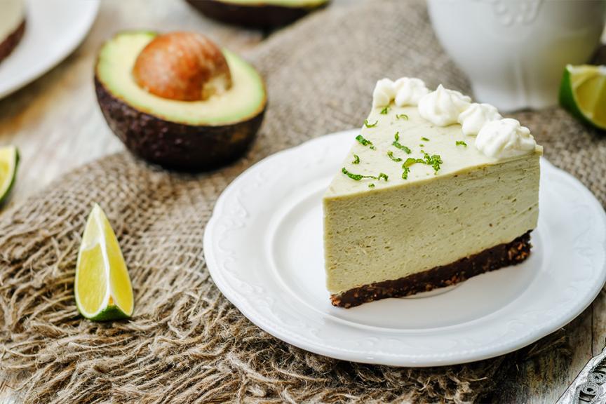 fetta di torta all'avocado in piatto bianco poggiata accanto a mezzo avocado aperto
