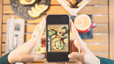 mano ragazza mantiene smartphone mentre scatta foto al suo brunch